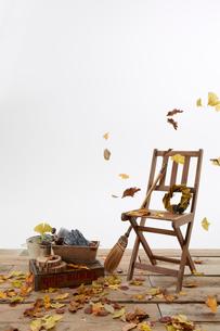 デッキの上の木の椅子とほうきと舞う枯葉の写真素材 [FYI01459752]