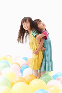 風船と背中合わせの双子の姉妹の写真素材 [FYI01459773]