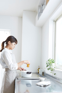 料理を鍋で作る女性の写真素材 [FYI01459834]