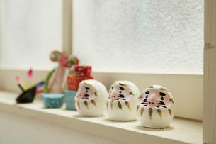 窓に置かれた3個の白いミニだるまと正月のオブジェの写真素材 [FYI01459857]