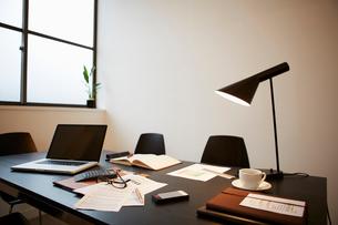 窓際の会議のテーブル上の書類にメガネとコーヒーカップの写真素材 [FYI01459933]