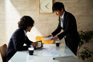 タブレットを見ながら打ち合わせをする2人のビジネスマンの写真素材 [FYI01459935]