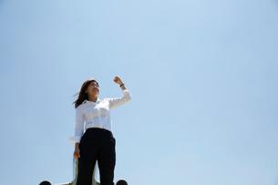 青空をバックにガッツポーズをしている白いブラウスの女性の写真素材 [FYI01459954]