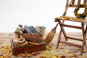 デッキの上の木の椅子と枯葉とほうきの写真素材 [FYI01460020]