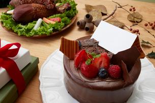 テーブルのクリスマスケーキと料理とプレゼントの写真素材 [FYI01460040]