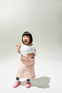 エプロンをしてボールをもつ女の子の写真素材 [FYI01460055]
