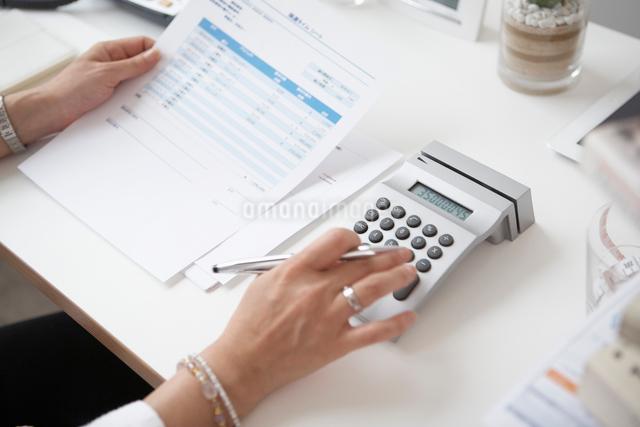 机で電卓で計算をする女性の手の写真素材 [FYI01460078]