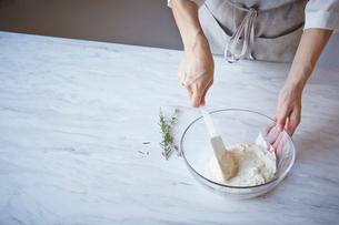 クリームチーズとローズマリーのソースを作っている女性の写真素材 [FYI01460125]
