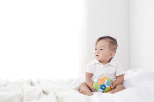 ベッドの上で遊ぶ赤ちゃんの写真素材 [FYI01460174]