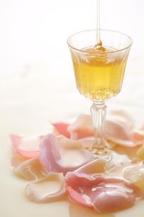 グラスに注がれるはちみつとピンクの花びらの写真素材 [FYI01460200]