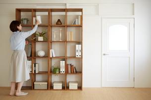 棚に本を片付ける女の人の写真素材 [FYI01460224]