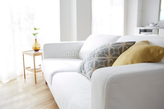 明るい窓際にあるソファーをリビングから見るの写真素材 [FYI01460275]