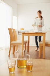 キッチンから物を運ぶ女性とリビングテーブルの飲み物の写真素材 [FYI01460308]