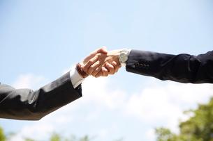 青空の下で握手をする男性の手元スーツの写真素材 [FYI01460360]