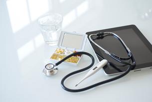 ケースに入ったビタミン剤とタブレットと聴診器と体温計の写真素材 [FYI01460393]