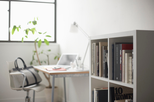 オフィス風景の机に置かれたノートパソコンと本棚の写真素材 [FYI01460416]