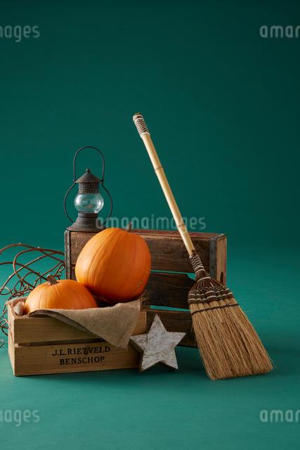 緑の背景に木箱に入った二個のハロウィンカボチャとほうきの写真素材 [FYI01460444]