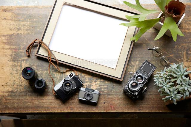 置いた額のまわりのアンティークなカメラとレンズの写真素材 [FYI01460489]