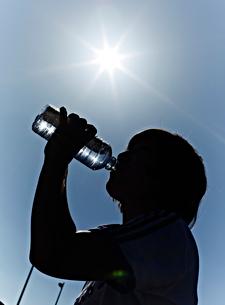 ペットボトルの水を飲む男性と太陽の写真素材 [FYI01460551]