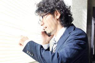 ブラインド越しに外を眺めながら電話をするビジネスマンの写真素材 [FYI01460725]