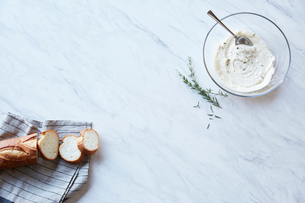 大理石に置かれたクリームチーズとローズマリーのソースとフランスパンの写真素材 [FYI01460729]
