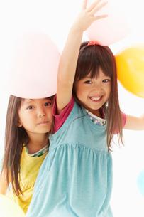 風船とカメラを見つめる双子の姉妹の写真素材 [FYI01460738]