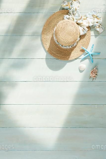 青い床の上の麦わら帽子と夏の日差しの写真素材 [FYI01460754]