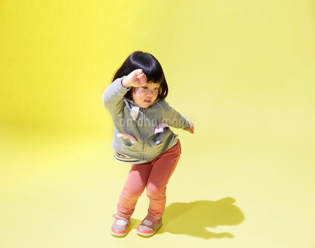 黄色い背景でダンスをする女の子の写真素材 [FYI01460755]