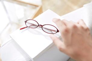 明るい窓際にあるソファーにおいているメガネを取ろうとする女性の手の写真素材 [FYI01460781]