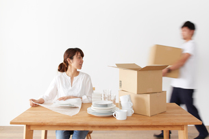 食器を梱包する女性と、ダンボール箱を運ぶ男性の写真素材 [FYI01460830]