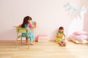 ピンク色の壁の子供部屋で勉強机に座っている女の子と床に座っている女の子の姉妹の写真素材 [FYI01460833]