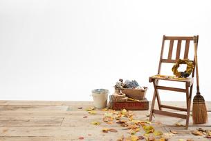 デッキの上の木の椅子と枯葉とほうきの写真素材 [FYI01460839]