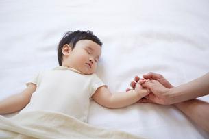寝ている赤ちゃんと手をつないでいるお母さんとお父さんの手の写真素材 [FYI01460881]