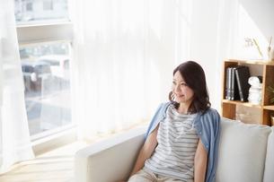ソファーに座る若い女性の写真素材 [FYI01460911]