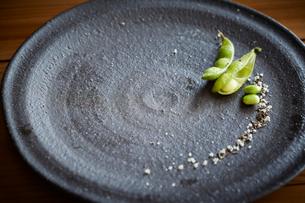 黒の皿の上の枝豆と塩の写真素材 [FYI01460933]