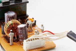 電子基盤の上で働く4個の人形の写真素材 [FYI01460960]