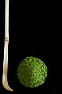 黒バックに盛られた抹茶の粉と茶杓の写真素材 [FYI01460975]