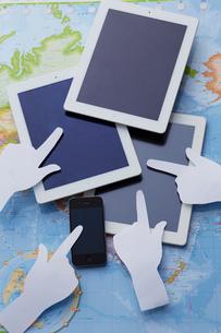 地図上の3台のタブレットとスマートフォンを指す白い紙の手の写真素材 [FYI01460988]