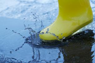 長靴で水溜りの水をはねる女性の写真素材 [FYI01461004]