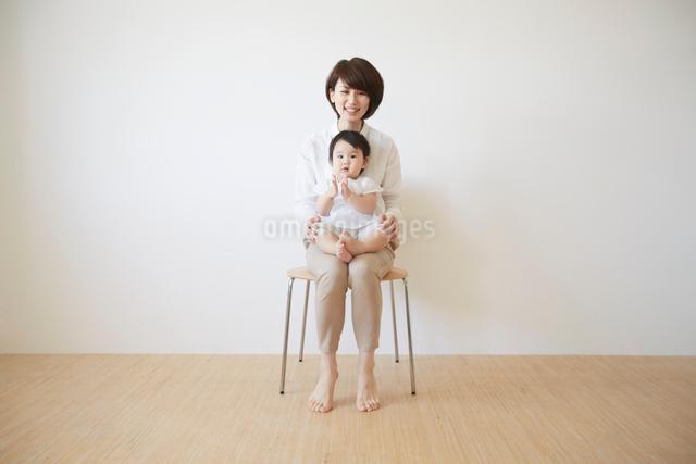 赤ちゃんを膝の上に座らせて椅子に座るお母さんの写真素材 [FYI01461009]