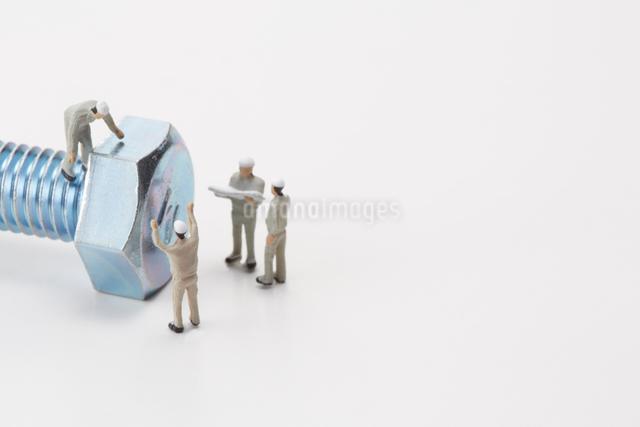 ボルトと作業着姿の4個の人形の写真素材 [FYI01461110]