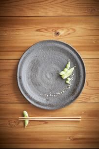 木テーブルに置かれた枝豆の八寸と箸の写真素材 [FYI01461138]