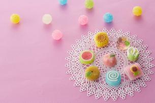 レースのコースターの上にカラフルな和菓子と飴玉の写真素材 [FYI01461162]