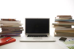 白い机のノートパソコンと本と資料の写真素材 [FYI01461186]