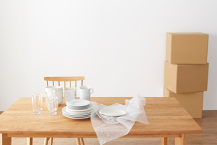ダイニングテーブルの上の食器と梱包材の写真素材 [FYI01461215]