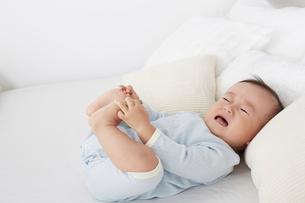 ベッドの上で泣く赤ちゃんの写真素材 [FYI01461258]