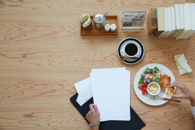 机の上のカフェご飯と書類の写真素材 [FYI01461355]