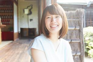 縁側に座り微笑む若い女性の写真素材 [FYI01461360]