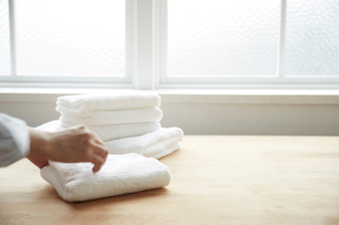 テーブルの上でタオルをたたむ女性の写真素材 [FYI01461376]