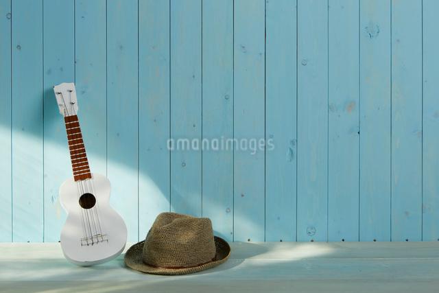 青い床と青い板壁とウクレレと麦わら帽子の写真素材 [FYI01461440]